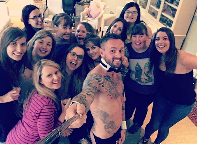 Butler taking a selfie with a group of women