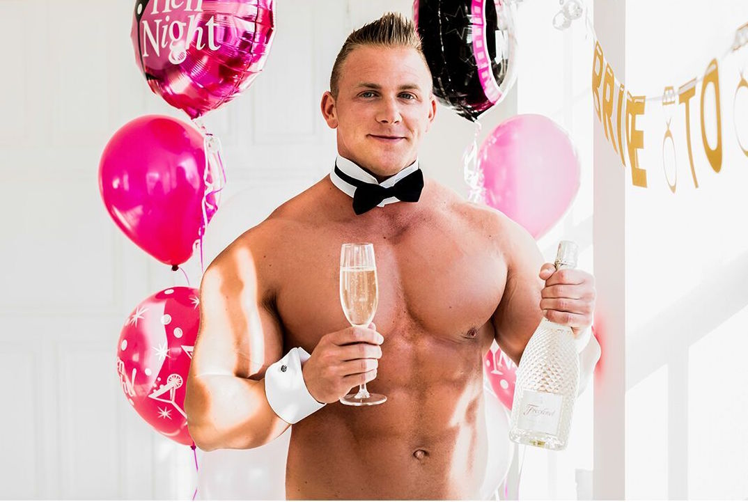 A buff butler holding a bottle of presecco