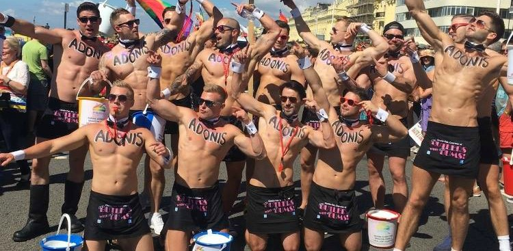 Large group of butlers outside with the word Adonis painted on their chests