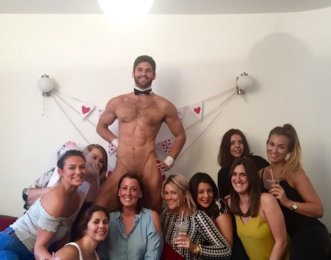 Naked butler stood behind group of women smiling