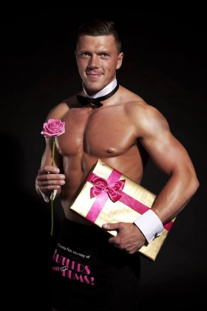 Butler holding a pink rose and box of chocolates posing for a photo