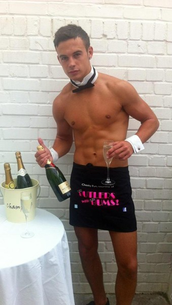 Butler popping open a bottle of champagne