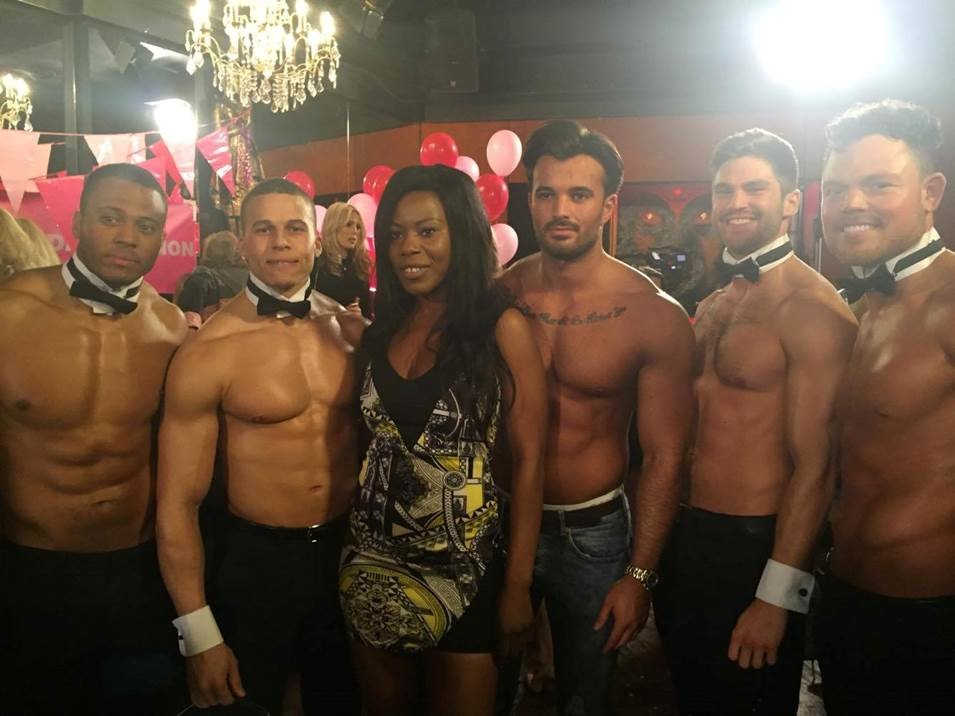 Group of butlers posing with a woman