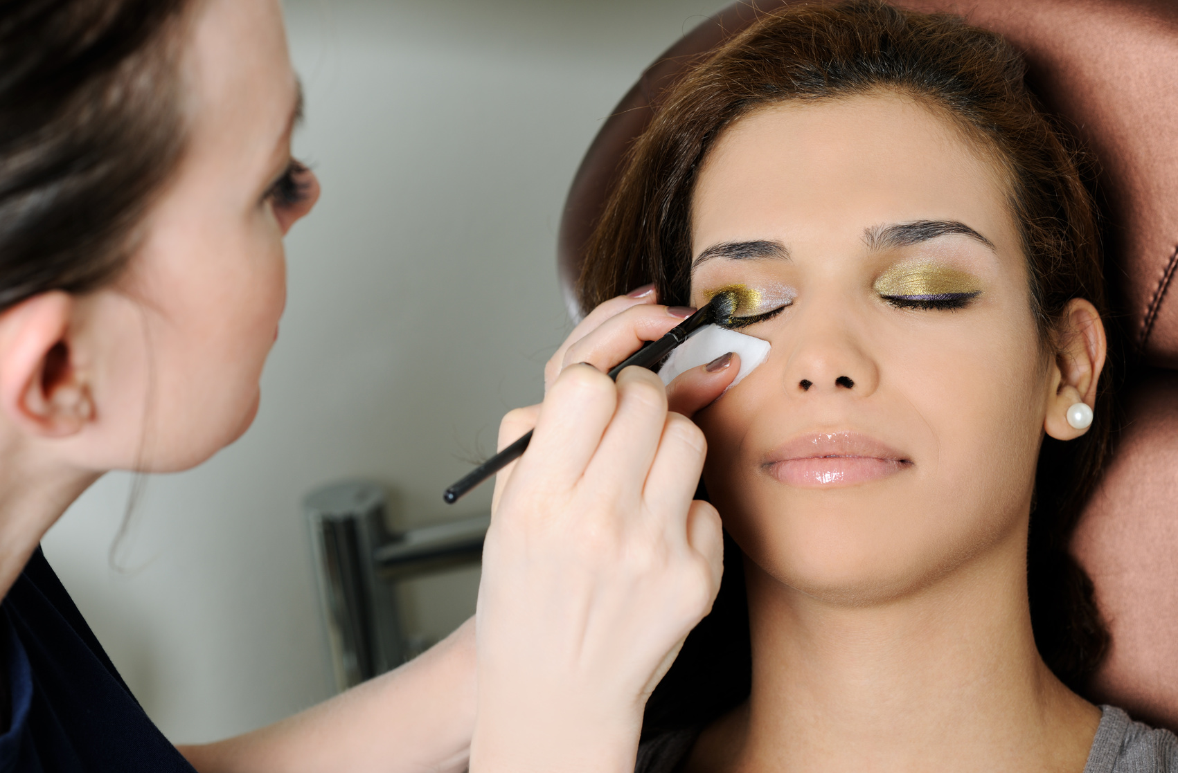 Woman having makeup applied to her eyelids