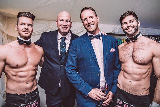 Butlers posing with two men in suits