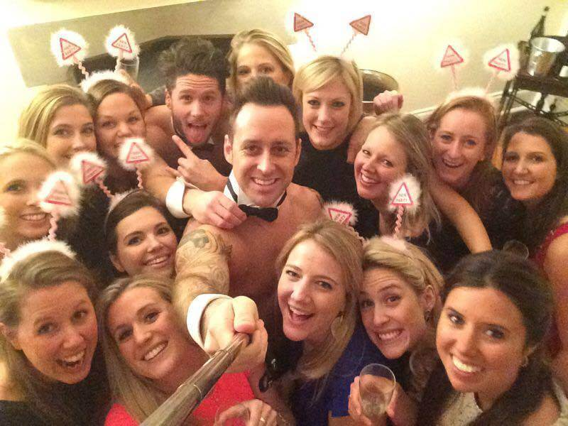 Butler taking a selfie with a large group of women at a hen party