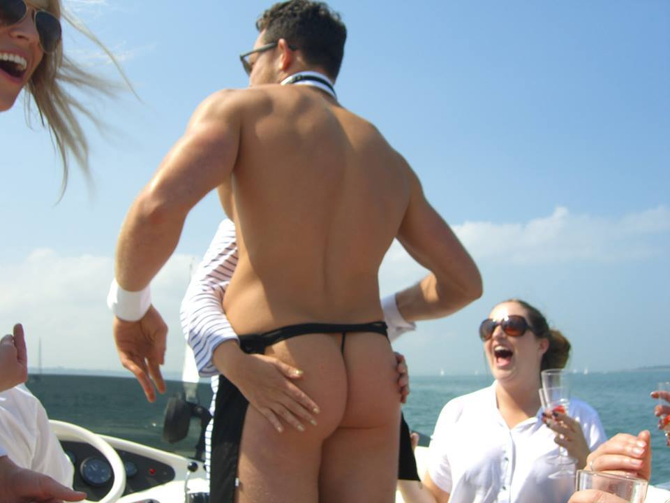 Woman reaching round a butler grabbing his bum on a boat
