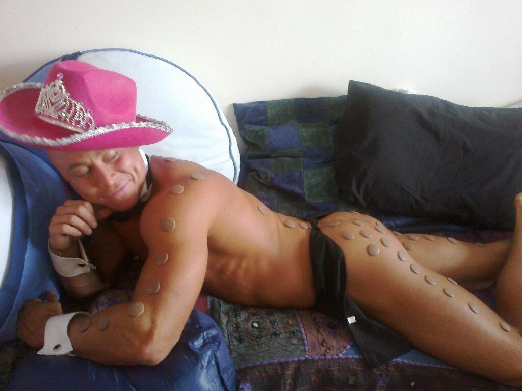 Butler lying on a sofa with chocolate discs on his body
