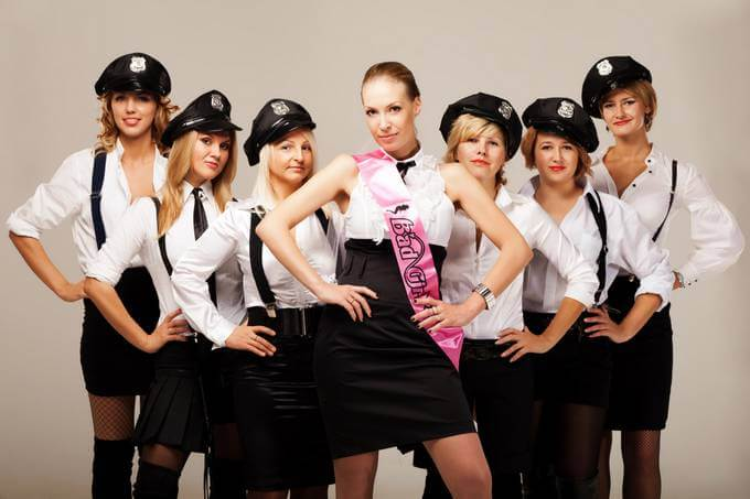 Women dressed as police women posing for a photo
