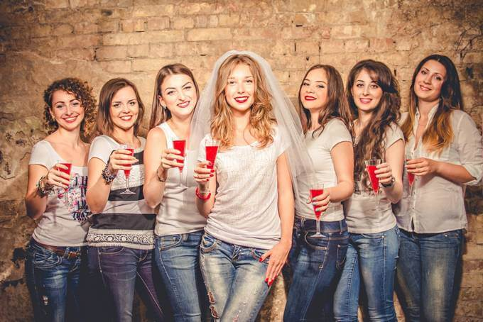Group of women wearing white tops and blue jeans holding drinks