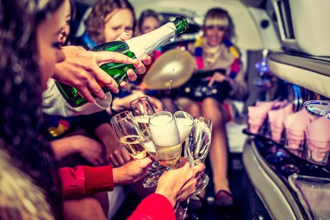 Woman holding glassses whilst someone pours champagne into them