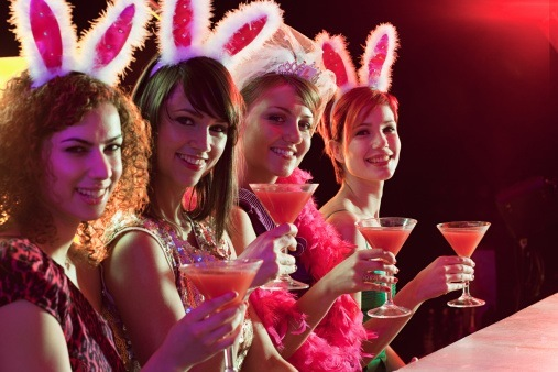 Women wearing bunny ears raising cocktail glasses