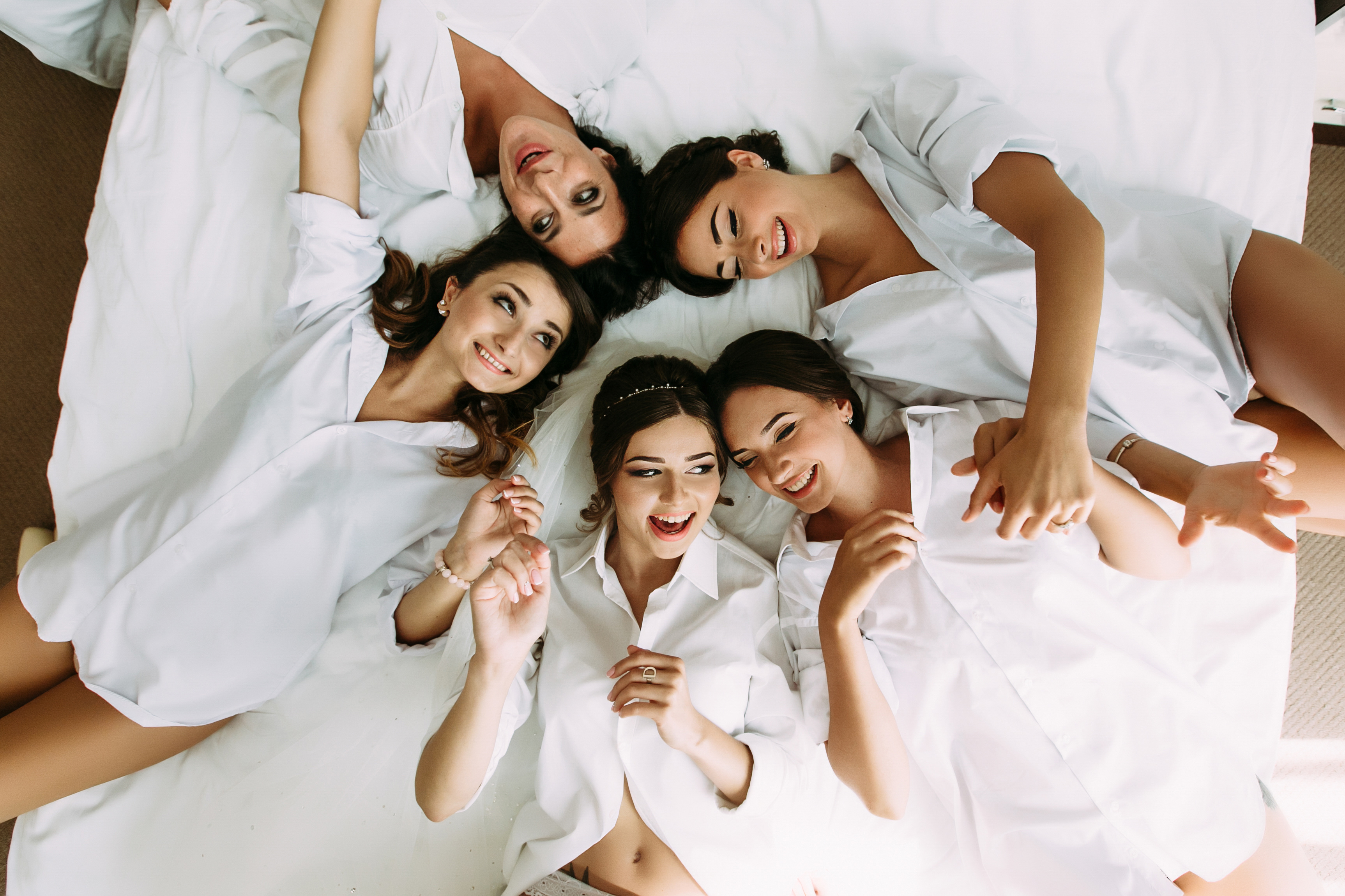 Group of women in white tops lying on a bed
