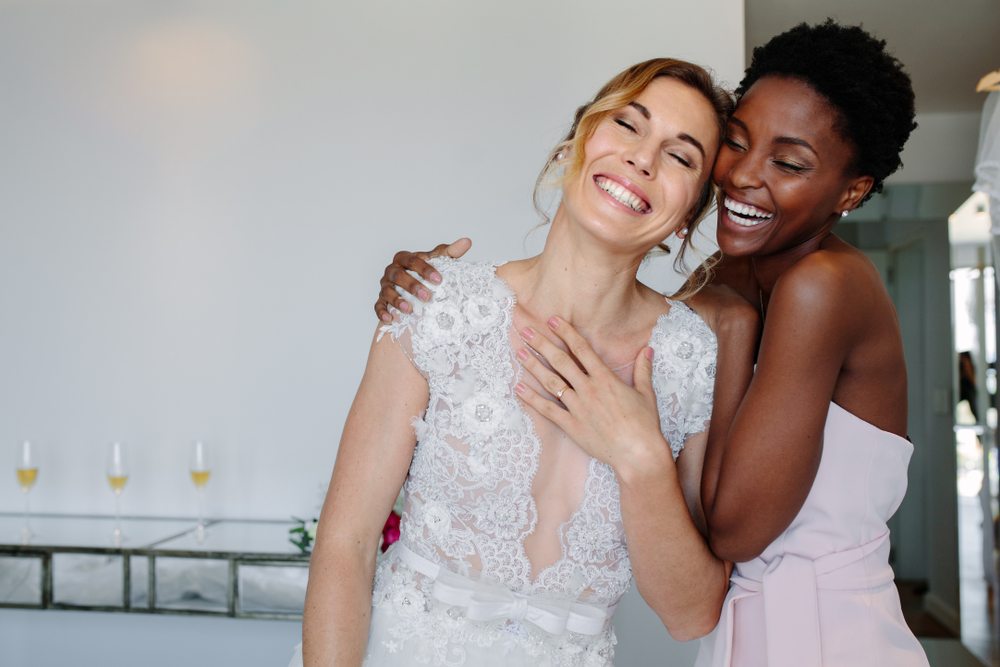 Gorgeous bride in wedding gown having fun with bridesmaid in hotel room.